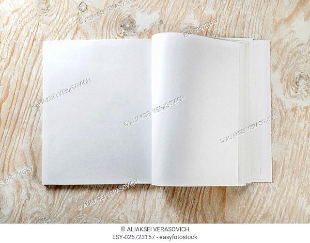 Blank opened book on light wooden background with soft shadows. Mock-up for graphic designers portfolios. Top view