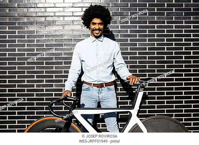 Mid adult man standing in front of black wall, holding his bicycle