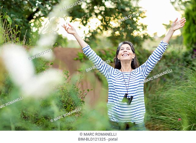 Hispanic woman standing with arms outstretched outdoors