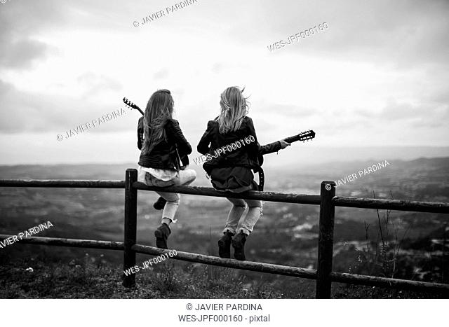 Two women sitting on wooden fence with guitars