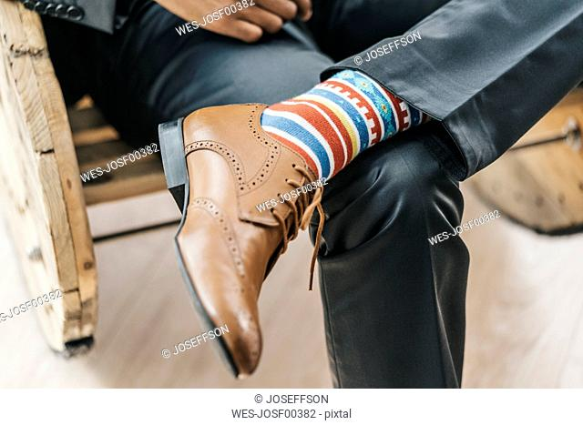 Young businessman sitting with legs crossed