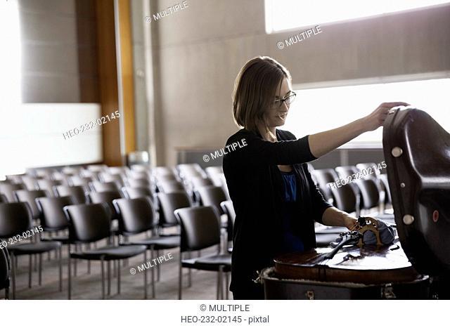 Female cellist opening cello case in auditorium