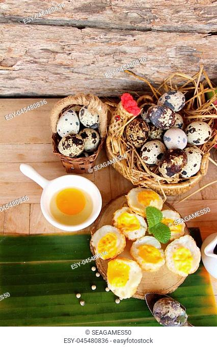 Grilled eggs with sauce on wood background