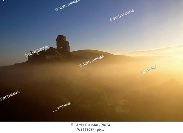 Corfe Castle at dawn on a misty autumnal morning, Dorset, England, UK