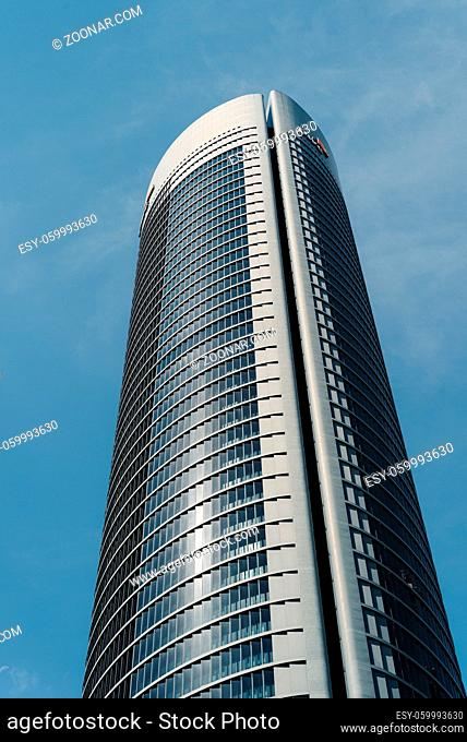 Madrid, Spain - June 14, 2020: Low angle view of skyscraper against sky. PWC tower in Four Torres Buisiness Area
