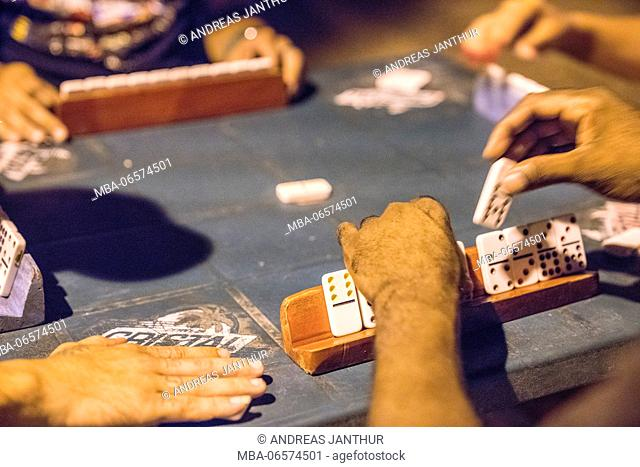 Dominoes in close up, game pieces, hands and table