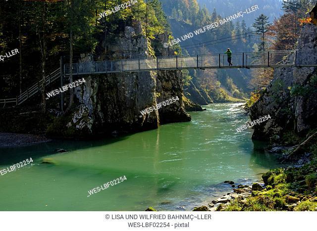 Austria, Tyrol, hiker on suspension bridge looking at Tiroler Ache in autumn