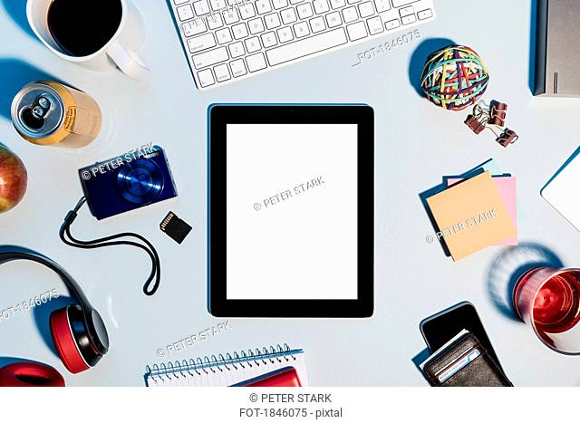 View form above digital tablet surrounded by office supplies on desk
