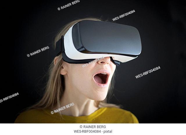 Astonished woman wearing Virtual Reality Glasses