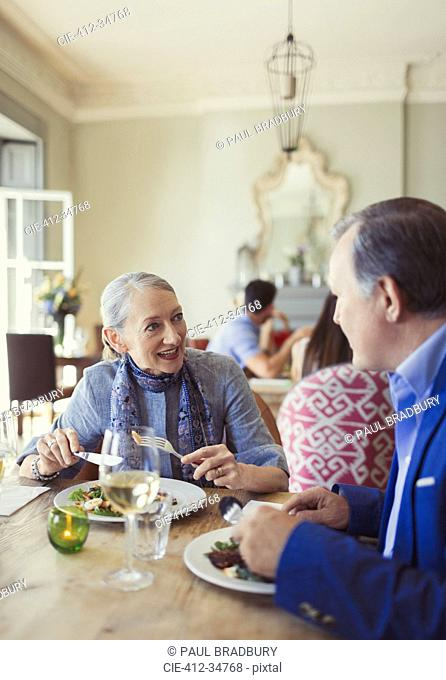 Senior couple talking and dining at restaurant table