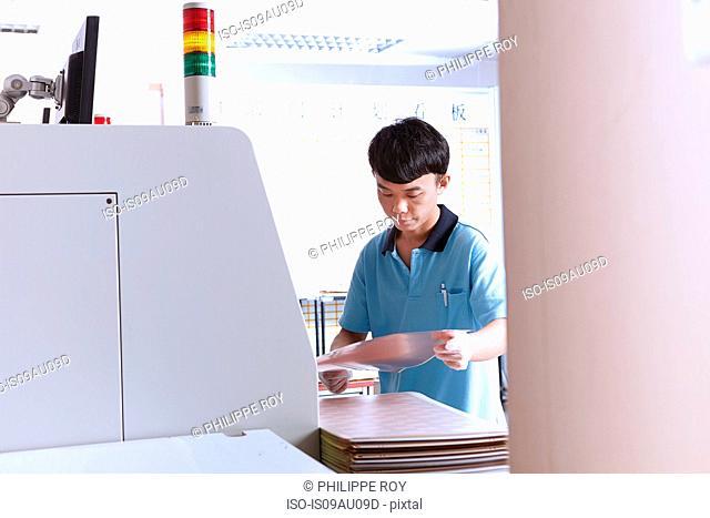 Young man using manufacturing machinery, making flexible circuits, looking down