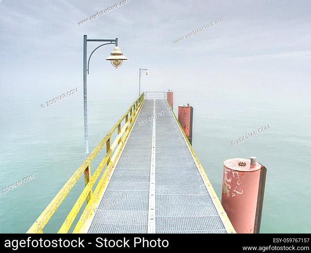 Abandoned steel mole in harbor above smooth water level. Long sea bridge ends in autumn mist