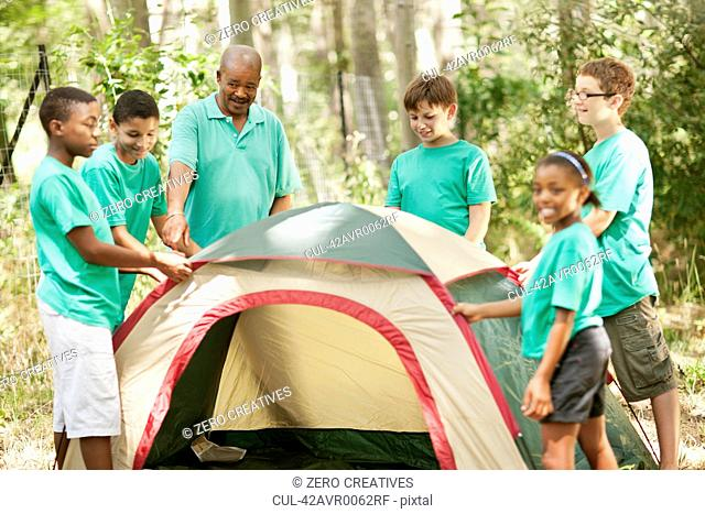 Students pitching tent with teacher