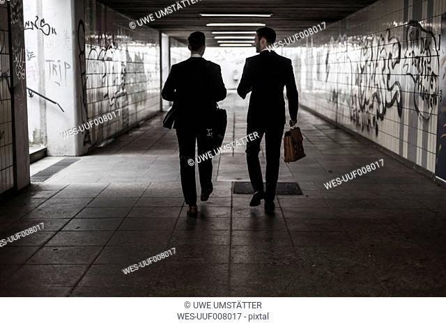 Two businessman walking in underpass, rear view