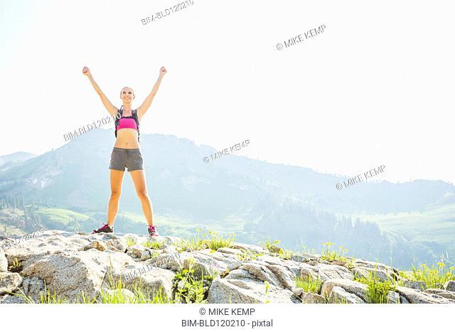 Caucasian woman cheering on rocky hilltop