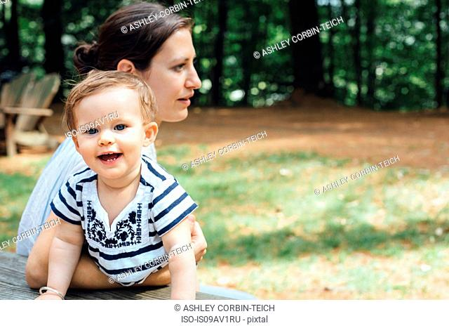 Young woman and baby daughter at forest picnic bench