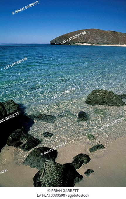 Near La Paz. Sea of Cortez. Bay beach. View on shoreline. Sand. Sun on green clear water. Rocks