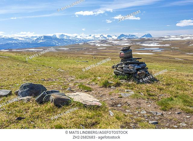 Landscape view over Sarek national park from Kungsleden with a heap of stones in the foreground showing the way on the trail, Stora sjöfallets national park