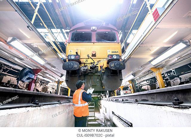 Engineer inspecting locomotive in train works