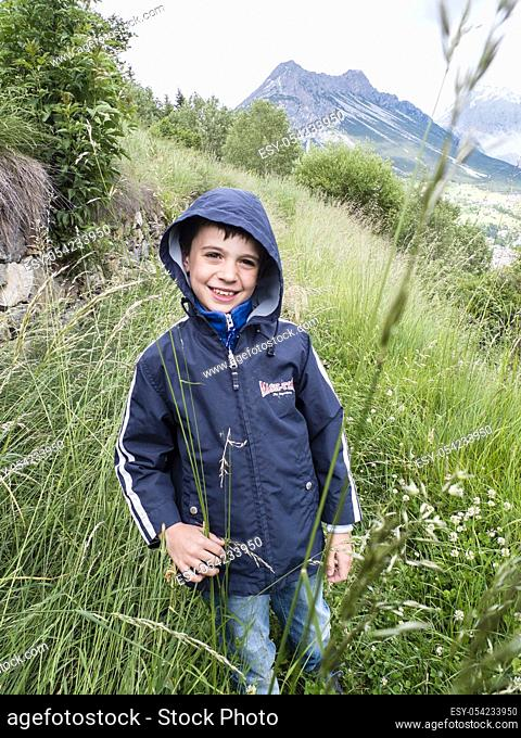Portrait of a child of 8 years in the mountains on the trail with tall grass, Valdidentro, Lombardy, Italy