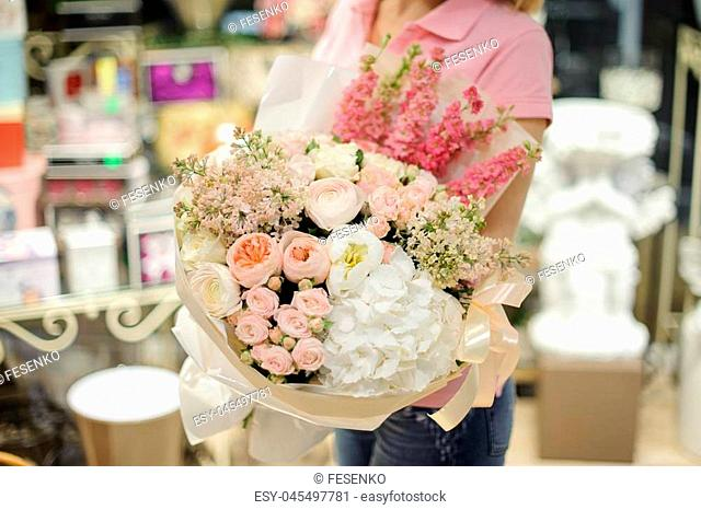 Girl in white shirt holding in her hands a beautiful big bouquet of rose colour hydrangeas, lilacs and ranunculuses