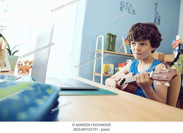Boy using laptop to play a song on an ukulele