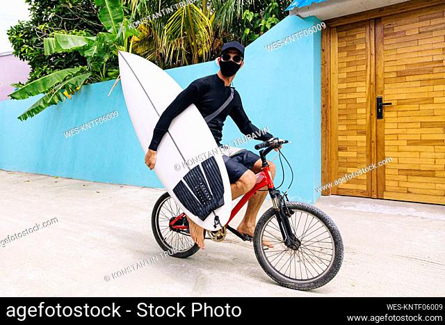Man wearing protective face mask carrying surfboard while riding bicycle on footpath at Huraa Island, Maldives
