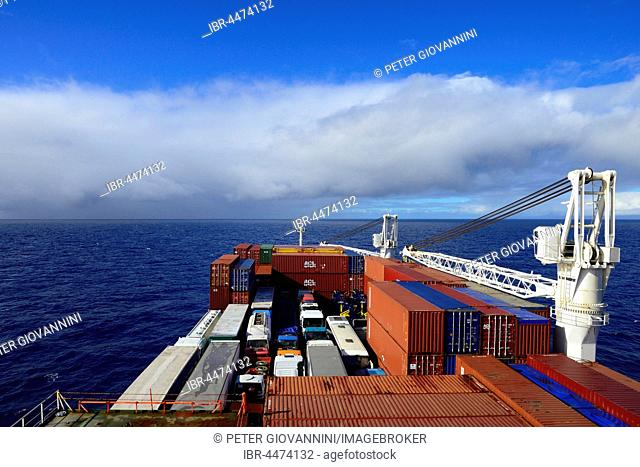 Cargo ship with vehicles and containers, open sea, Atlantic with clouds