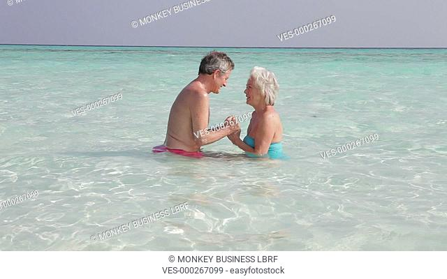 Senior couple standing in sea holding hands.Shot on Canon 5d Mk2 with a frame rate of 30fps