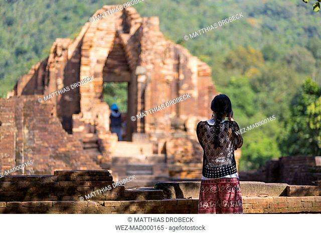 Vietnam, Quang Nam Province, woman taking picture of Cham temple complex My Son
