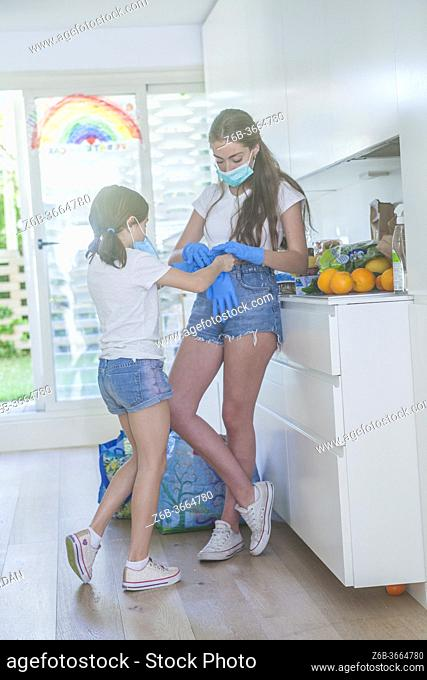 2 girls putting on gloves, they wear masks