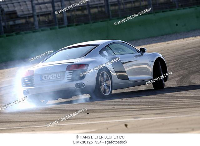 Audi R8 4.2 FSI, model year 2007-, silver, driving, diagonal from the back, rear view, test track, Drift, drifting, puffing away tyre