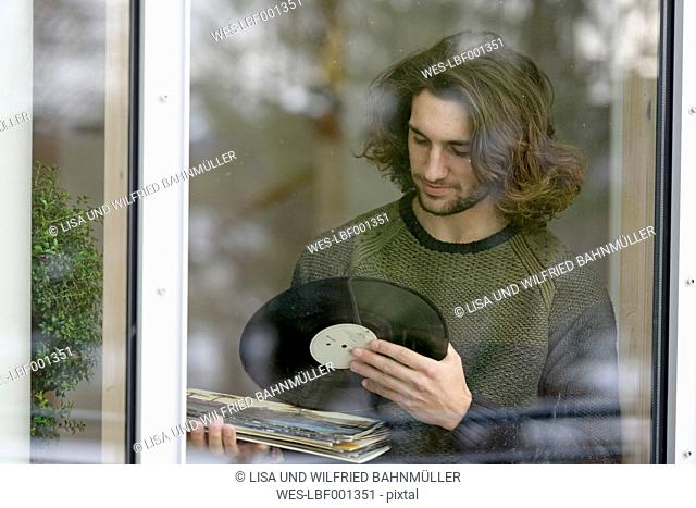 Young man with records standing behind window pane
