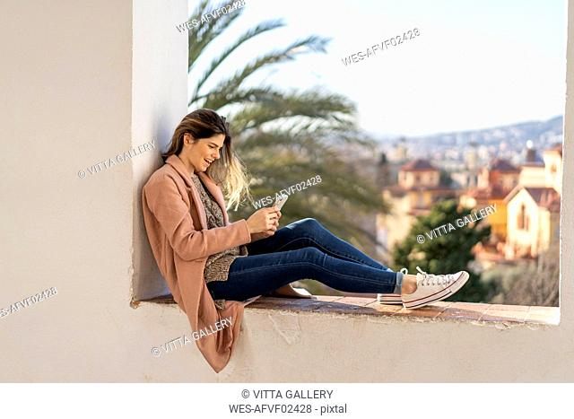 Laughing young woman sitting on a wall using cell phone