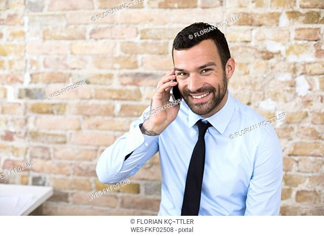 Portrait of smiling businessman on the phone at brick wall