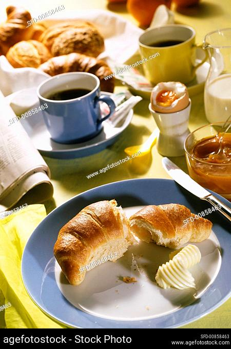 Breakfast of croissant, jam, egg and coffee