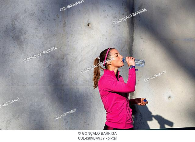 Young woman drinking water from water bottle
