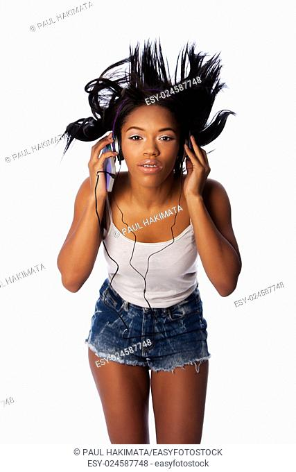 Beautiful teenager jamming listening to music with wild hair, on white