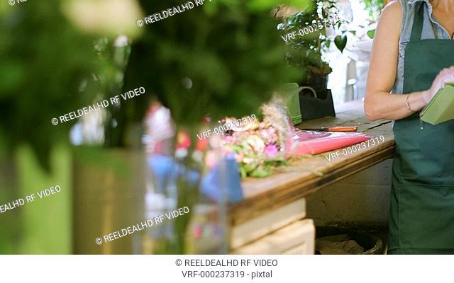 A Florist stands in her shop using her digital tablet