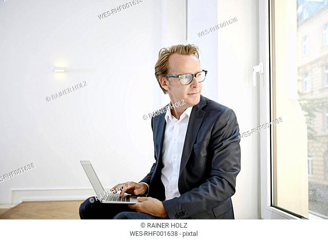 Businessman with laptop looking through window