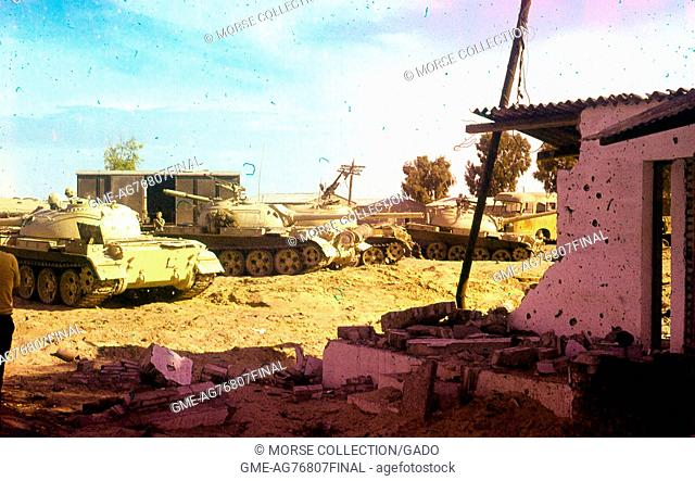 View of Israeli military tanks and vehicles idling in the dirt outside of a destroyed building, in Gaza, Israel, November, 1967