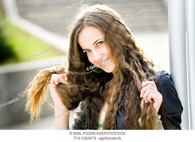 Playing with her long hair happy young woman
