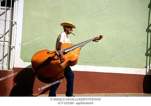 Bass Player carrying his instrument in a Street of Trinidad de Cuba. Cuba