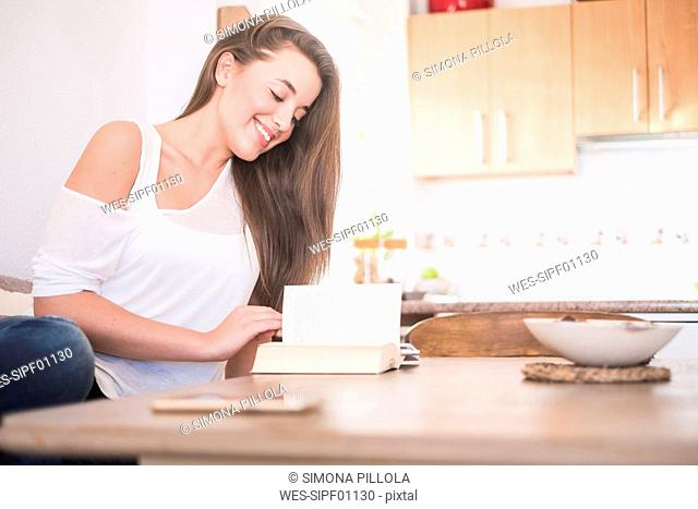 Smiling young woman sitting at table in the kitchen reading book