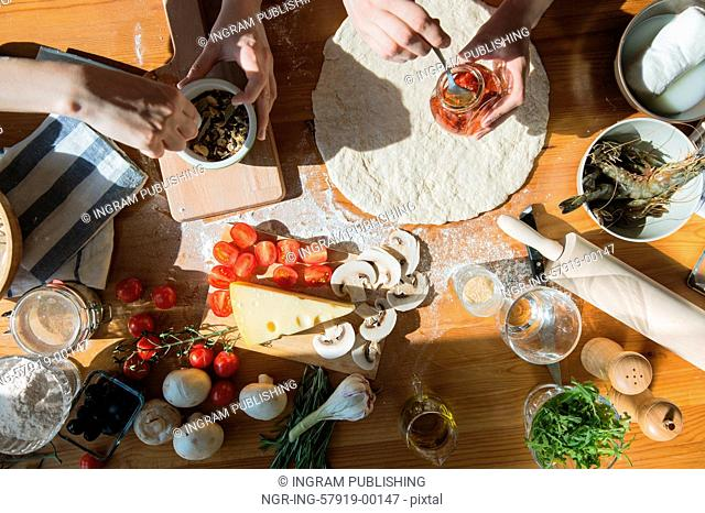 Two women cooking pizza at home. Filling pizza with ingredients. Top view. Overhead view