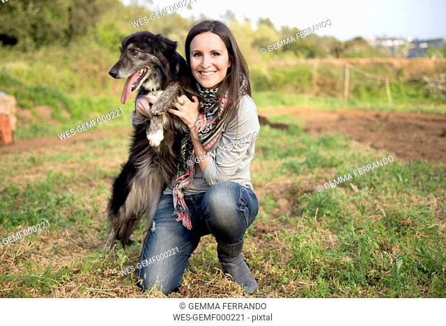Smiling woman holding dog outdoors