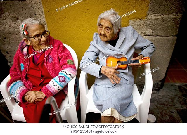 Isabel Minor Alarcon, 99, right, jokes holding her toy guitar as Luz Maria Rodríguez, 92, looks on in Our Lady of Guadalupe Home for the Elderly, Mexico City