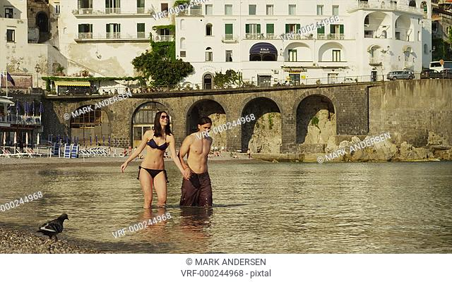 WS Young couple wading in water on Amalfi Beach / Italy