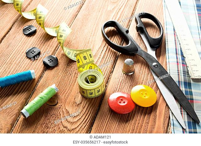 Bright image of sewing kit accessories on wooden table