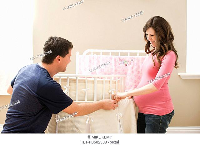 USA, Utah, Lehi, Young pregnant woman and mid adult man holding hands by playpen